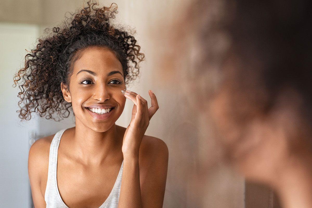 mulher negra passando creme facial