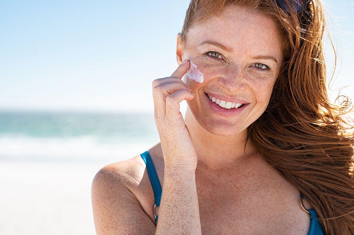 mulher passa protetor solar no rosto