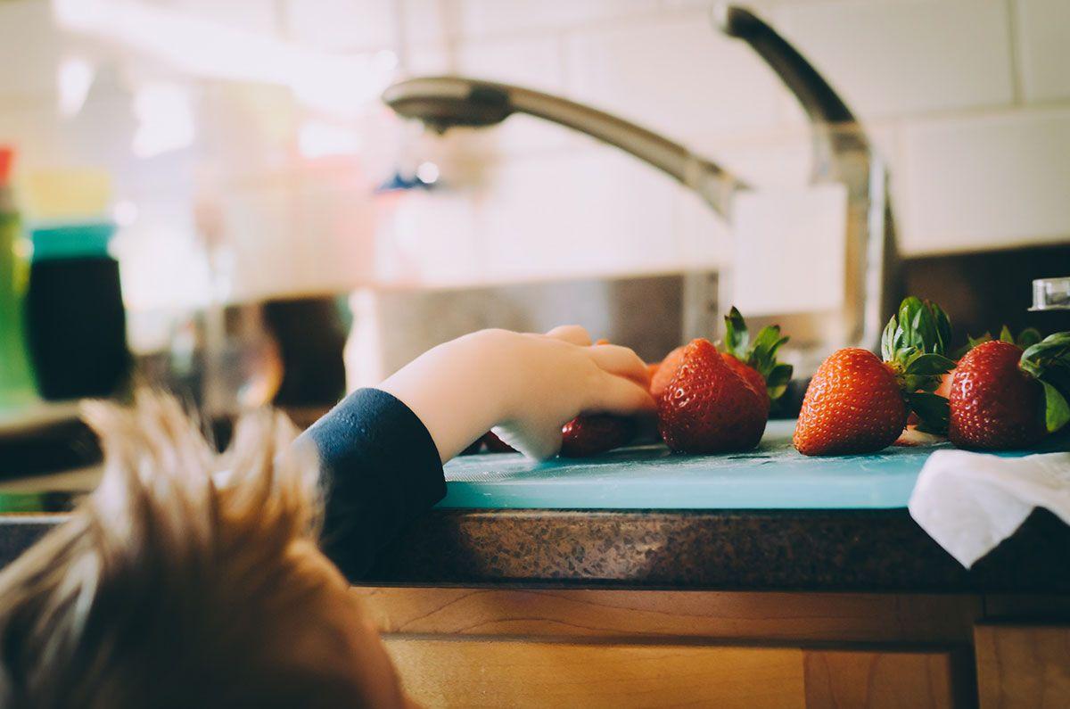 mão de criança pegando fruta