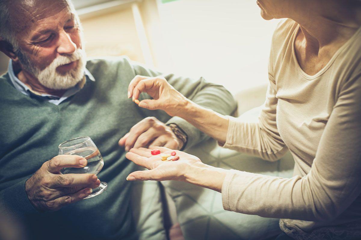 mulher dando remédio a idoso