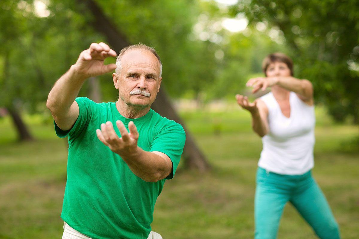 casal idoso fazendo tai chi